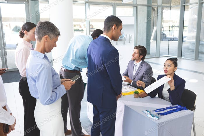Rear view of diverse business people checking in at conference registration table in office lobby