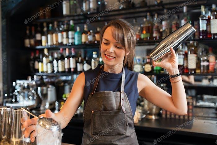 barmaid with shaker preparing cocktail at bar