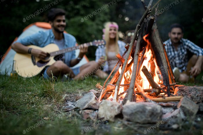 Happy friends enjoying music near campfire at night