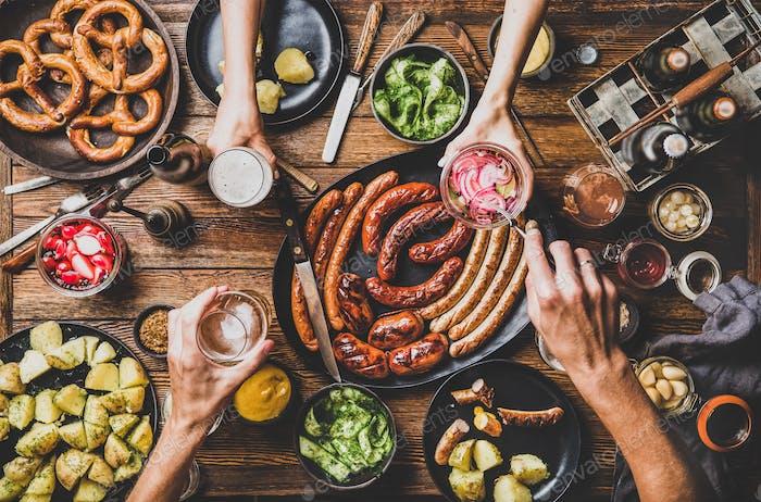 Flat-Lay vom Oktoberfest Esstisch mit Bier, Snacks und Menschen