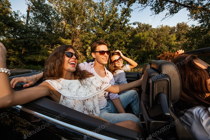 Company of young people riding in a cabriolet on the road on a warm sunny day. Two beautiful girls