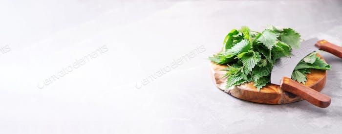 Brennnesseln, Urtica. Grüne Brennnesselblätter im Holztopf auf grauem Hintergrund. Alternative Kräuter