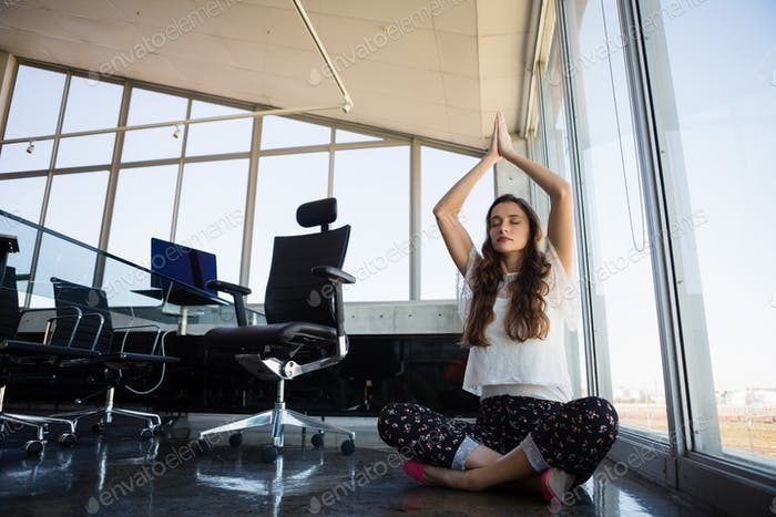 Businesswoman with eyes closed doing yoga on floor