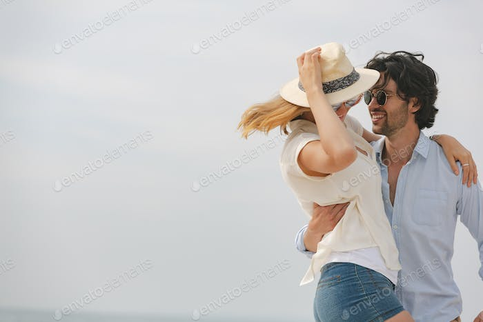 Couple looking at each other and dancing on beach on sunny day