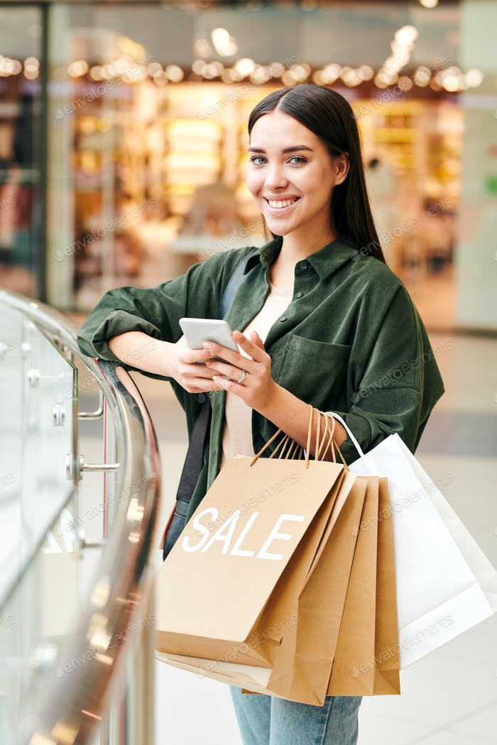 Young contemporary female shopaholic with toothy smile using smartphone