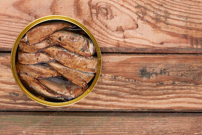 Sprats in a tin can on a wooden surface