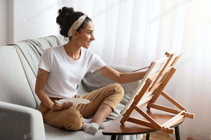 Inspired young woman sitting on couch and painting