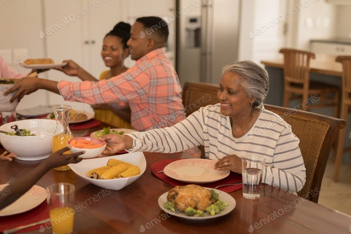 Side view of  African American senior woman passing food to her grandson on dinning table at home