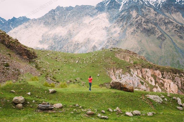 Stephantsminda, Georgia. Frau Tourist sind fotografiert Frühling Berglandschaft