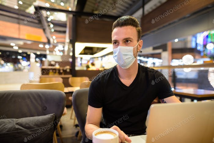Serious man sitting at coffee shop wearing face mask and using laptop computer while thinking