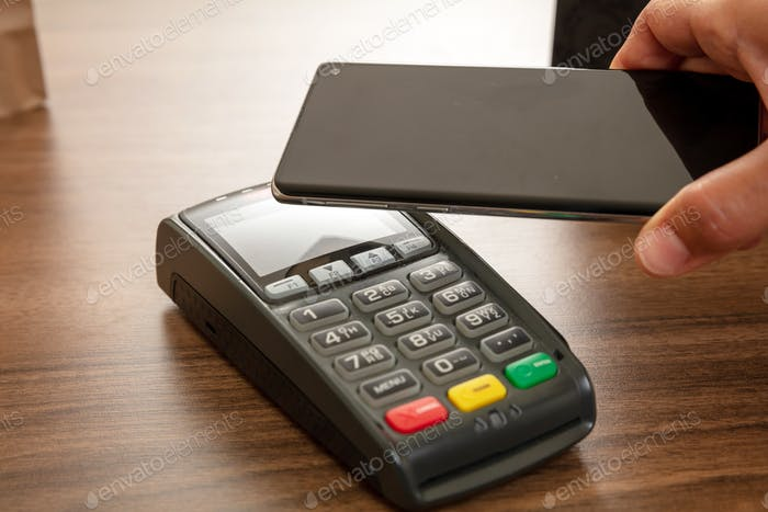 POS terminal for payment with smartphone, nfc technology. Customer hands closeup view