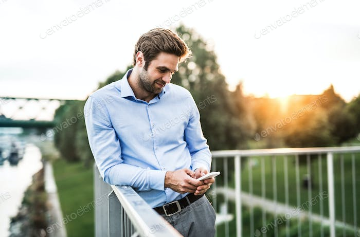A young businessman with smartphone standing on a bridge at sunset, leaning on a railing.