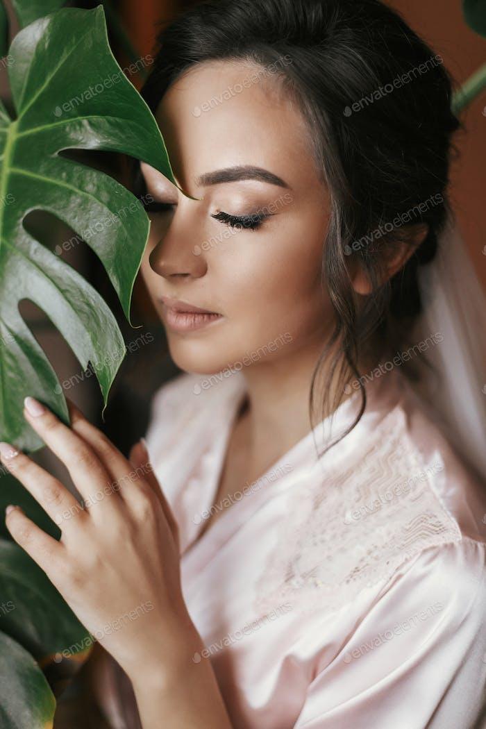 gorgeous bride portrait with monstera leaf