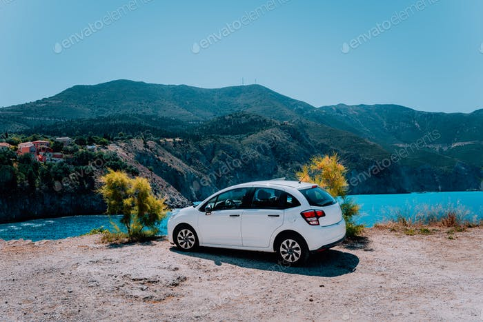 Vacation travel with car concept. Rental hired car in front of amazing bay with turquoise water