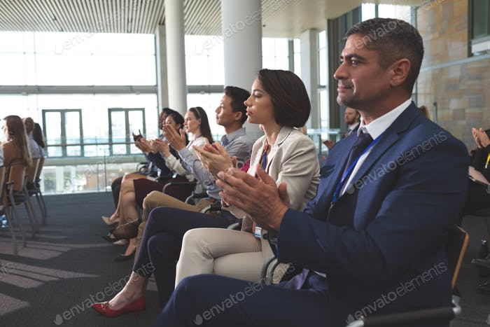 Side view of diverse business people clapping at a business seminar in office building