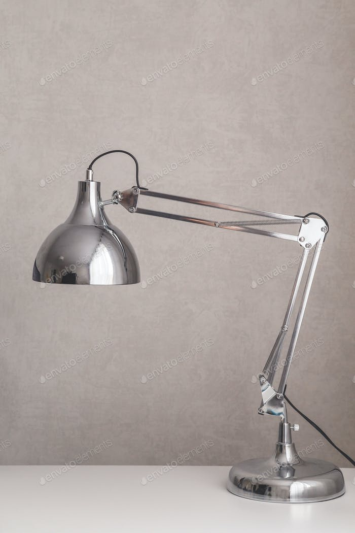 Modern chrome desk lamp switched on