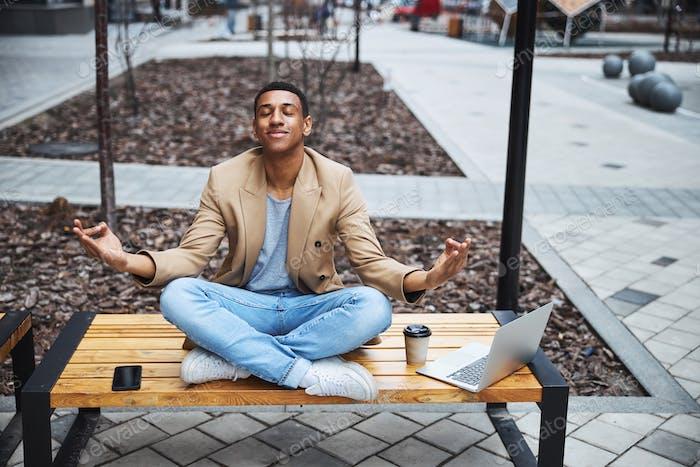 Kind international man meditating on the street