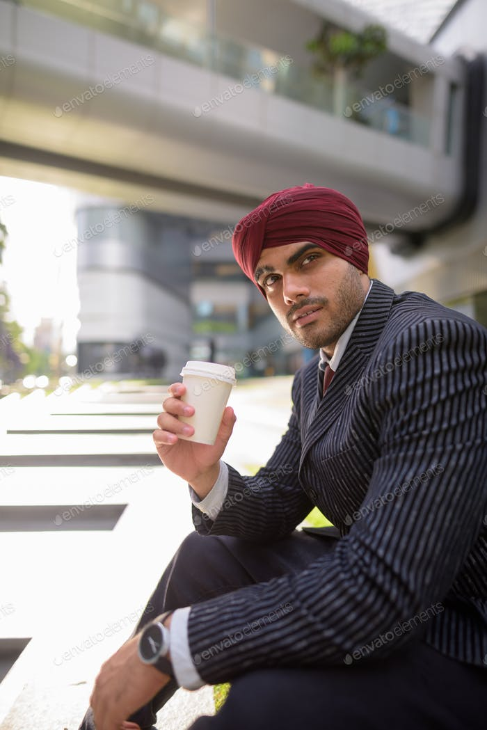 Indian businessman sitting outdoors in city while holding coffee cup