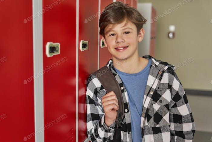 Happy schoolboy is standing in the corridor