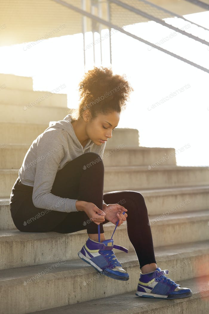 Young exercise woman tying her shoelaces