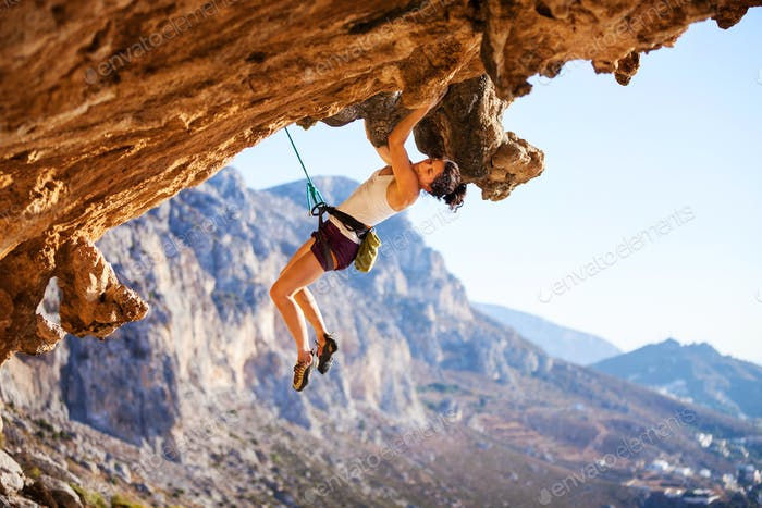 Young female rock climber on a face of cliff