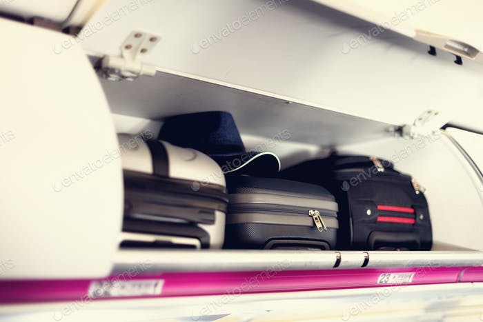 Hand-luggage compartment with suitcases in airplane. Carry-on luggage on top shelf of plane. Travel