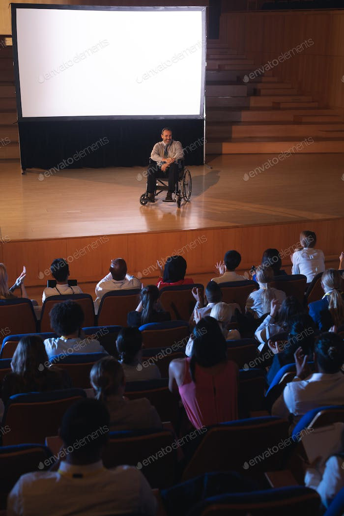 Businessman sitting on a wheelchair and giving presentation to the audience in the auditorium