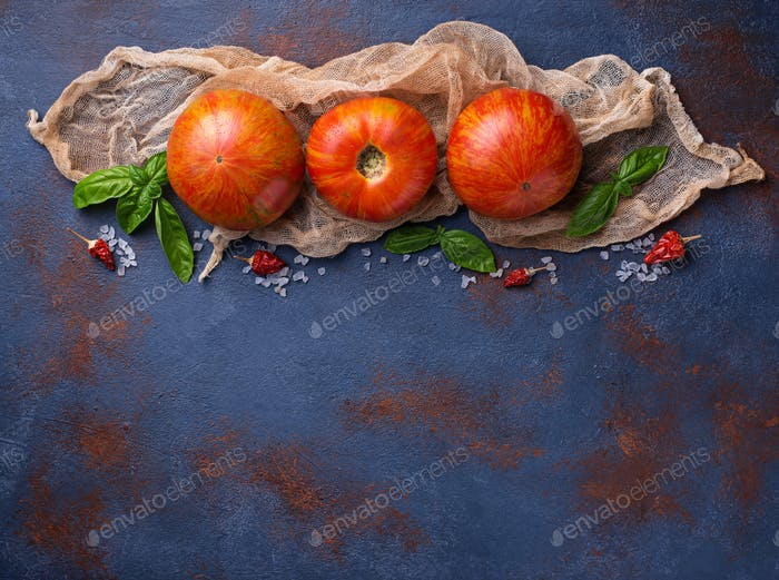 Fresh tomato on blue rusty background.