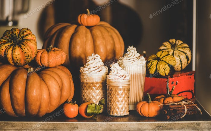 Pumpkin latte coffee in glasses among pumpkins and cinnamon sticks