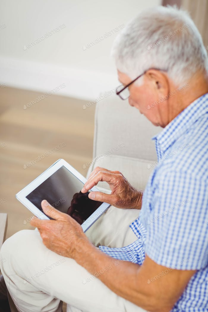 Senior man sitting on sofa and using digital tablet in living room