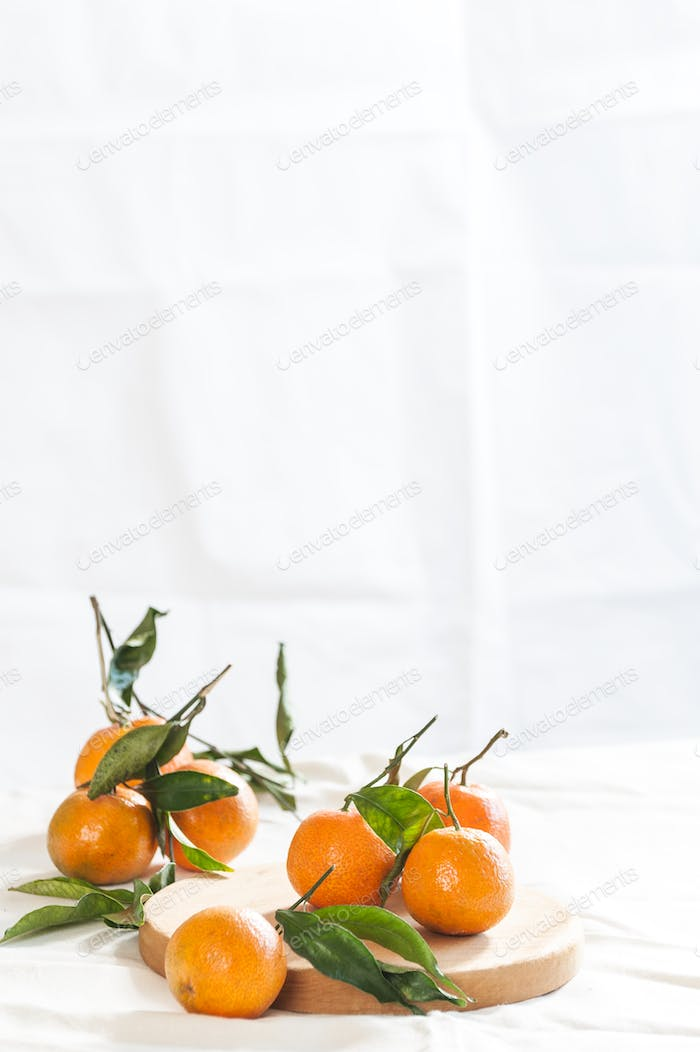 Ripe mandarins with twigs on a round board. A photo with negativ