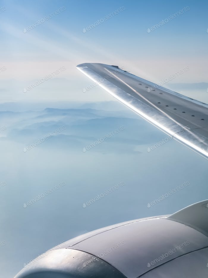 wing of aircraft and view of mountains and sea