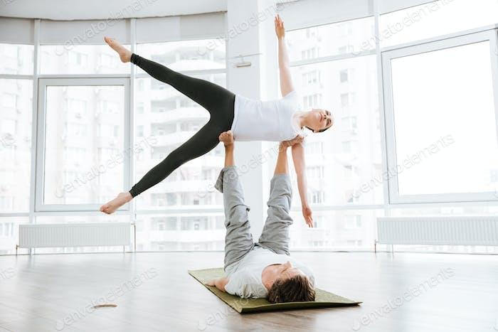 Glückliches paar tun acro yoga