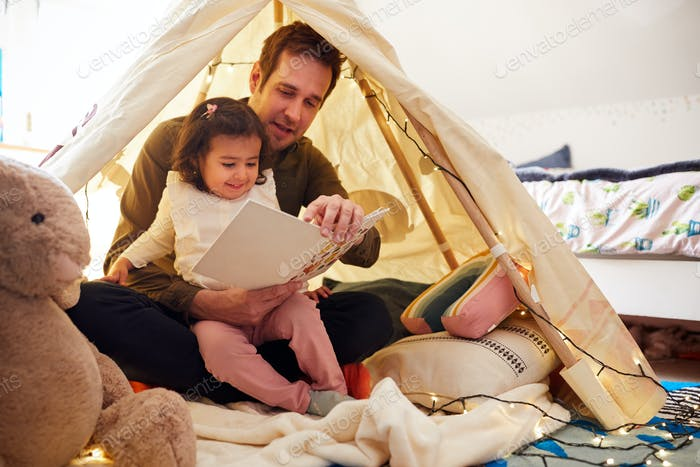 Single Father Reading With Daughter In Den In Bedroom At Home