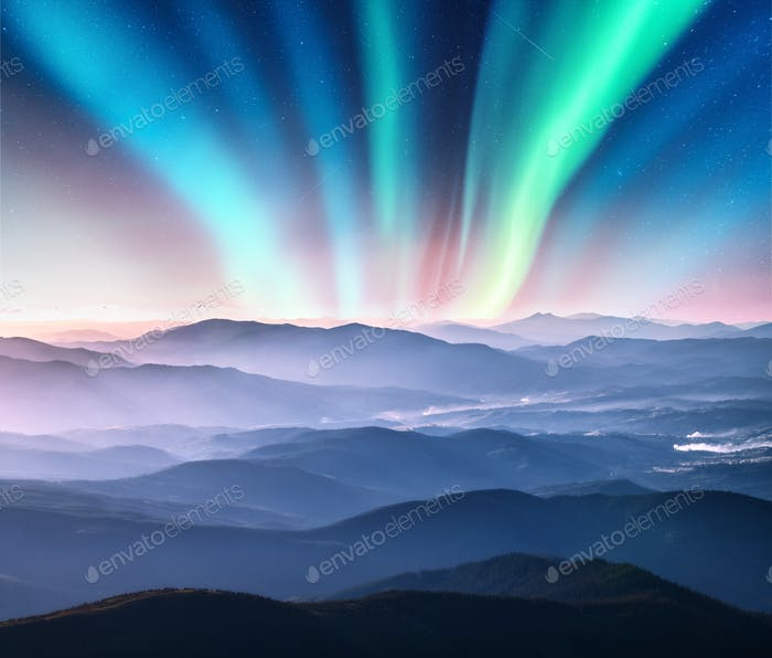 Aurora borealis above the mountain valley in low clouds at night