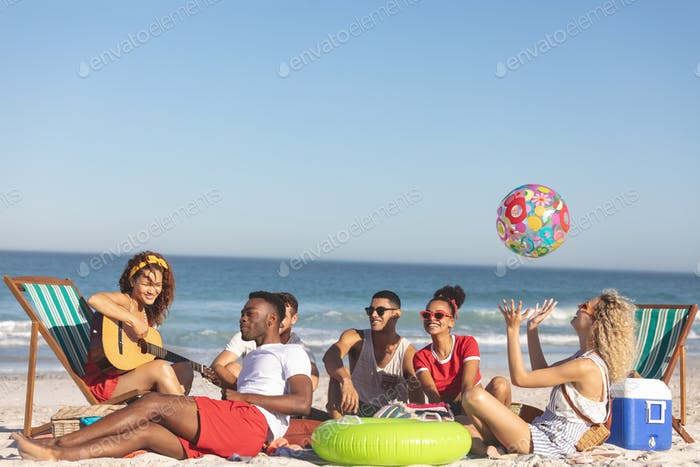 Front view of group of happy diverse friends having fun together on the beach