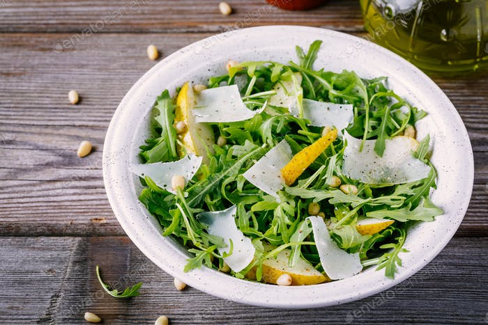 green salad bowl of arugula with pear, parmesan cheese and pine nuts
