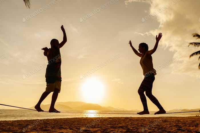 couple balancing slackline on the beach