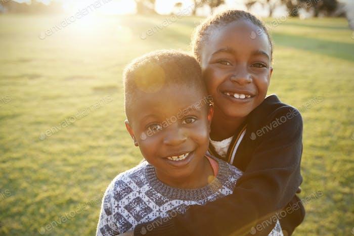 Afrikanische Grundschule Junge und Mädchen umarmt im freien