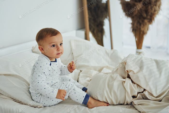 Cute little boy sits on the bed. Interior and design of beautiful modern bedroom at daytime