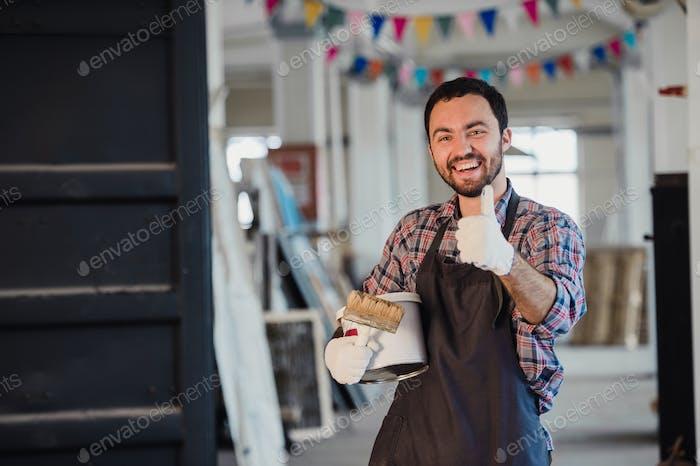 Handyman mit Pinsel in seiner Werkstatt mit Daumen nach oben