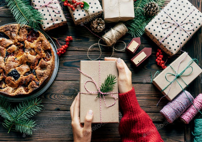 In the center of the composition, women's hands hold one gift box. Festive Christmas Eve concept.