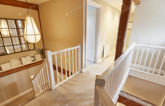 Interior View Of Beautiful Stairs And Landing With Exposed Wooden Beams In Family House