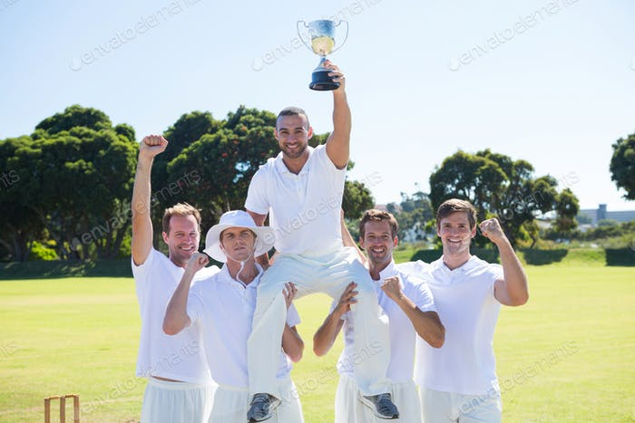 Happy cricket team with throphy standing on field