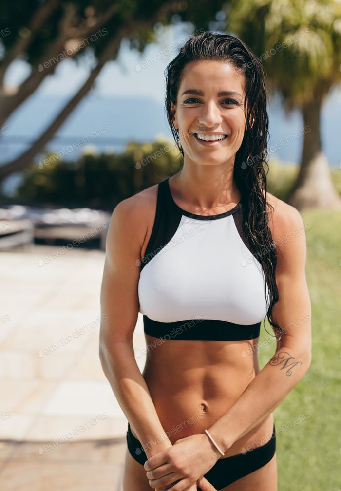 Beautiful young woman smiling in sports bra