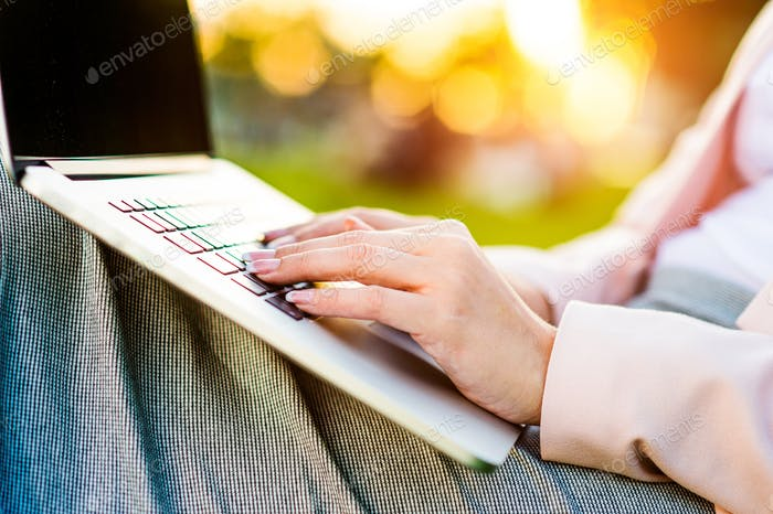 Business woman sitting in a park