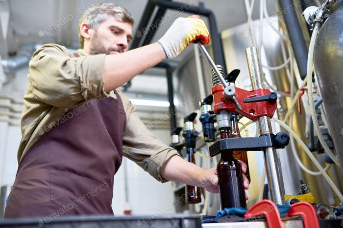 Concentrated busy brewer closing beer bottle at plant