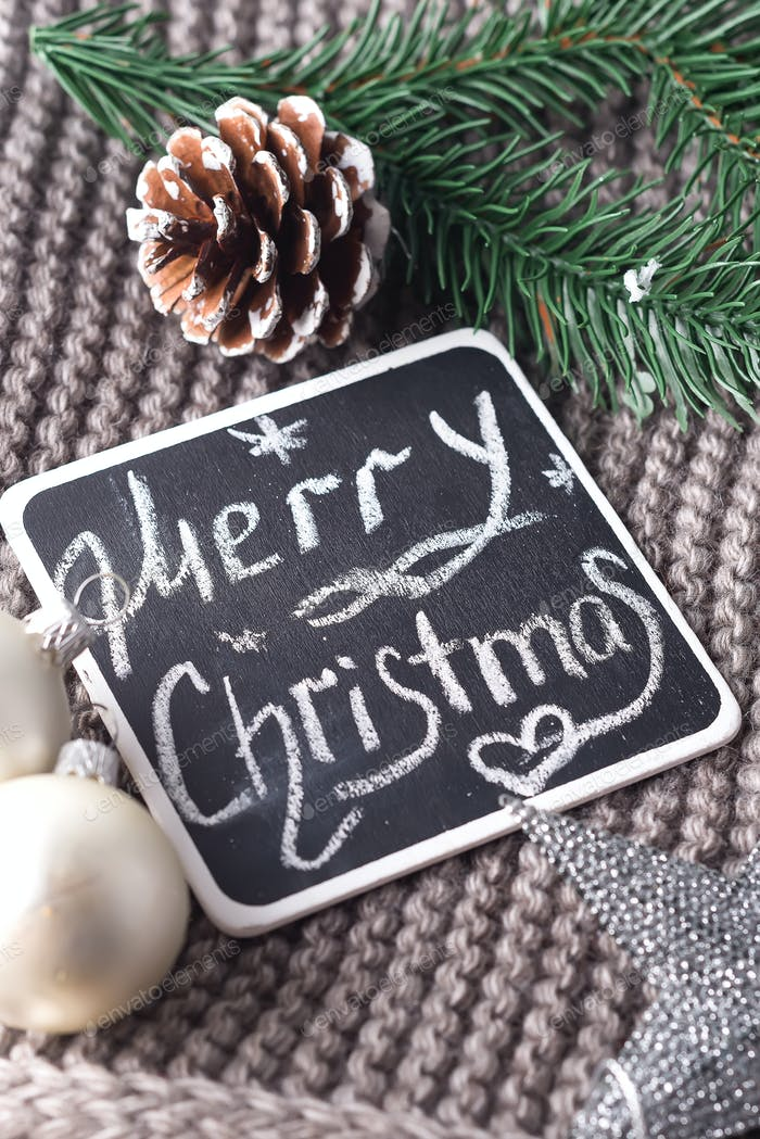 Christmas wishes written in chalk on a blackboard- Happy Christmas on warm scarf and toys