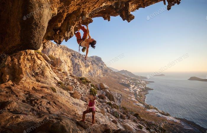 Junge Frau führen Klettern auf einem Dach in Höhle