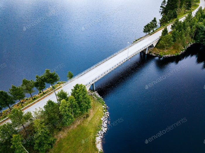 Aerial view of bridge road near blue lake in summer landscape in Finland